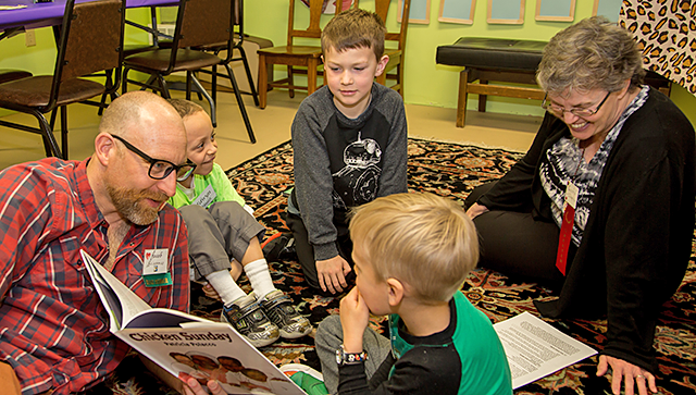 Photo of book being read to children